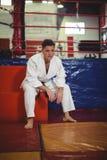 Karate gracza obsiadanie w sprawności fizycznej studiu obrazy stock