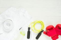 Karate-, judo-, Taekwondo likformig, handskar och hopprep på vit bakgrund royaltyfri foto