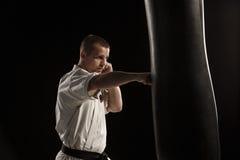 Karate kick in a punching bag Royalty Free Stock Photo