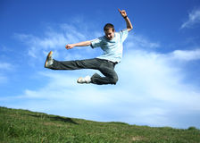 Karate kid. Young boy jumping on a grass Royalty Free Stock Photography