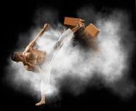 Karate mężczyzny łamanie z nogi drewnianą deską zdjęcie royalty free