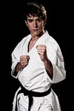 Karate male fighter young high contrast. On black background royalty free stock photos