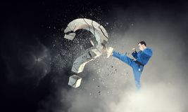 Karate man in action. Mixed media. Determined man in kimono breaking stone question mark. Mixed media Stock Photography