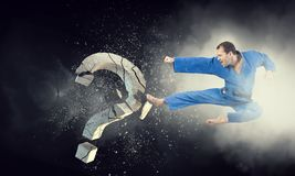 Karate man in action. Mixed media. Determined man in kimono breaking stone question mark. Mixed media Royalty Free Stock Images