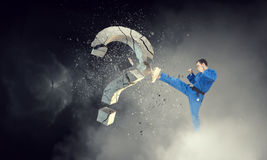 Karate man in action. Mixed media. Determined man in kimono breaking stone question mark. Mixed media Royalty Free Stock Photo