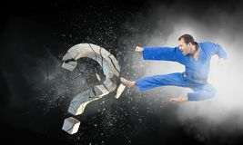 Karate man in action. Mixed media. Determined man in kimono breaking stone question mark. Mixed media stock image