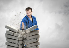 Karate man in blue kimino. Young determined karate man breaking with hand concrete bricks Stock Photography
