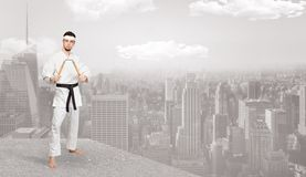 Karate man doing karate tricks  on the top of a metropolitan city. Young karate trainer doing karate tricks on the top of a metropolitan city stock photo