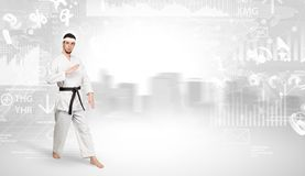 Karate man doing karate tricks on the top of a metropolitan city. Young karate trainer doing karate tricks on the top of a metropolitan city royalty free stock images
