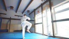 Black belt karate fighter training hight kick. Karate. Man in kimono doing high kick with his foot stock video footage