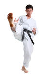 Karate. Man in a kimono hits foot. On the white background stock image