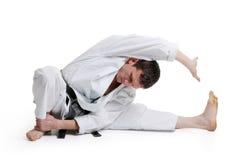 Karate, man in a kimono limberingup. On a white background stock photography