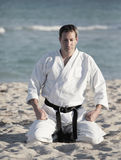Karate man meditating on the beach Royalty Free Stock Photos