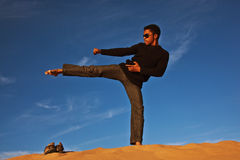 Karate man on sand dune Stock Photos