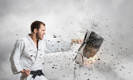 Karate man in white kimino. Young determined karate man breaking personal computer Stock Photography