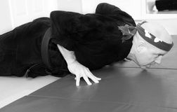 Karate Master Doing Fingertip Pushups. Middle aged black belt karate sensei doing fingertip pushups stock image