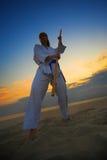 Karate op zonsondergangstrand stock foto's