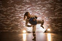 Karate opleiding in de studio Een klein meisje die beenaanval tonen stock afbeelding