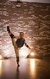 Karate opleiding in de studio Een klein meisje die haar tonen die uitrekken zich stock fotografie