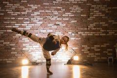 Karate opleiding in de studio met gele lichten Een klein meisje die beenaanval tonen royalty-vrije stock afbeelding