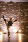 Karate opleiding in de studio met gele lichten Een klein meisje die haar tonen die uitrekken zich royalty-vrije stock afbeelding