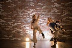 Karate opleiding in de studio Twee meisjes die karateaanval met een been opleiden stock afbeelding
