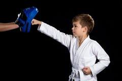 Karate opleiding, rechtstreeks geraakt met dichtgeklemde vuist aan het blauwe ponsenstootkussen stock foto's