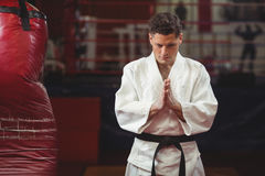 Karate player in prayer pose. In fitness studio royalty free stock image