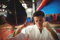 Karate practicante del combatiente del karate con el saco de arena Foto de archivo libre de regalías