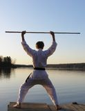 Karate Sunrise. Teen boy practicing karate form at the lake Stock Image