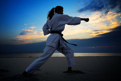 Karate on sunset beach. Young woman training karate on sunset beach Royalty Free Stock Photography