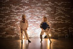 Karate training in the studio. Two little girls standing in karate training clothes. Mid shot royalty free stock image
