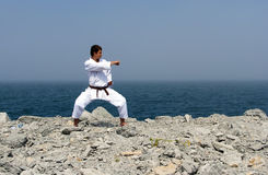Karate trains on the shores of sea Stock Photos