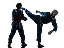 Karate vietvodao martial arts man woman couple silhouette. One caucasian men women couple exercising karate vietvodao martial arts in silhouette studio isolated Stock Image