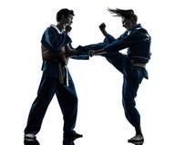 Karate vietvodao martial arts man woman couple silhouette. One caucasian men women couple exercising karate vietvodao martial arts in silhouette studio isolated Royalty Free Stock Photos