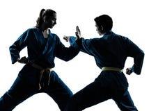 Karate vietvodao martial arts man woman couple silhouette. One  men women couple exercising karate vietvodao martial arts in silhouette studio isolated on white Stock Image