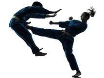 Karate vietvodao martial arts man woman couple silhouette. One  men women couple exercising karate vietvodao martial arts in silhouette studio isolated on white Stock Images