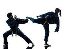 Karate vietvodao martial arts man woman couple silhouette. One men women couple exercising karate vietvodao martial arts in silhouette studio isolated on white Royalty Free Stock Photo