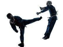 Karate vietvodao martial arts man woman silhouette. One causasian manman women couple exercising karate vietvodao martial arts in silhouette studio  on white Stock Images