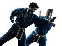 Karate vietvodao martial arts man woman silhouette. One  men women couple exercising karate vietvodao martial arts in silhouette studio isolated on white Royalty Free Stock Image