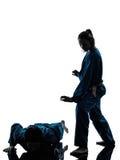 Karate vietvodao martial arts man woman silhouette. One  men women couple exercising karate vietvodao martial arts in silhouette studio  on white background Stock Image
