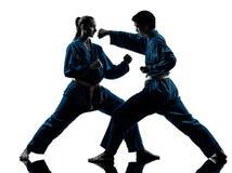 Karate vietvodao martial arts man woman silhouette. One  men women couple exercising karate vietvodao martial arts in silhouette studio  on white background Stock Images