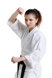 Karate. Young girl in a kimono. With a white background royalty free stock images