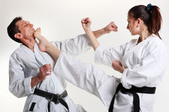 Karate. Young girl and a men in a kimono. With a white background. Battle sports capture Stock Photos