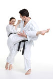 Karate. Young girl and a men in a kimono. With a white background. Battle sports capture Royalty Free Stock Photo
