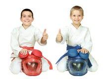 Karatebarn sitter i en ritual poserar med hjälmar och pekar det isolerade fingret Fotografering för Bildbyråer