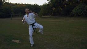 Karateförlagen i kamp för kimonoövningsskugga, gör en serie av sparkar, och sparkar, utbildar i morgonen i staden arkivfilmer