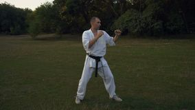 Karateförlagen i kamp för kimonoövningsskugga, gör en serie av sparkar, och sparkar, utbildar i morgonen i staden stock video
