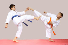 In karategi boys are beating kicks on the mats Stock Images