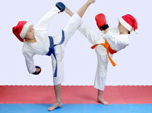 In karategi and cap of Santa Claus sportsmens are beating kicks Royalty Free Stock Photos